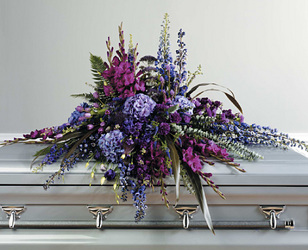 Mixed casket spray of mixed purple flowers from Bunn Flowers & Gifts, local florist in Pittsburg, TX