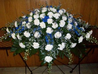 Casket spray of blue delphinium and white carnations from Bunn Flowers & Gifts, local florist in Pittsburg, TX