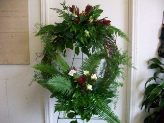 Grapevine wreath with fresh greenery and flowers on a stand from Bunn Flowers & Gifts, local florist in Pittsburg, TX